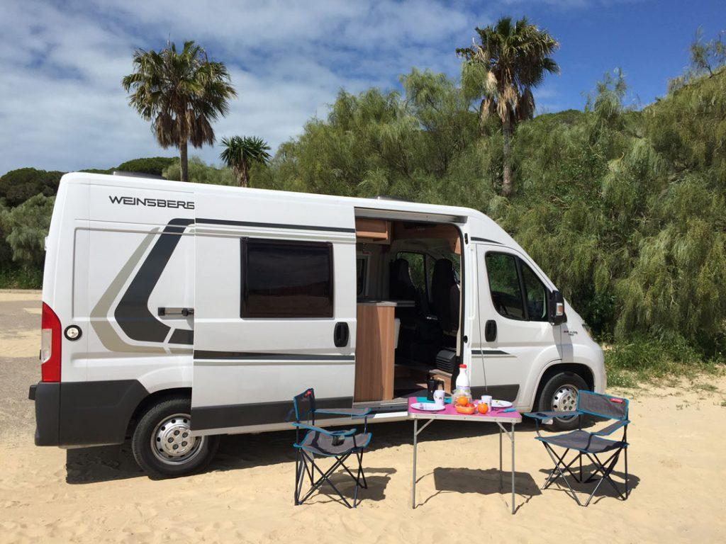 une table et quelques chaises extérieures inclus dans la location du camping-car